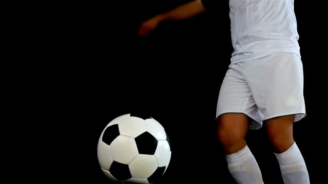 Football game. Soccer action. Goal keeper/footballer kicking a ball, slow motion video