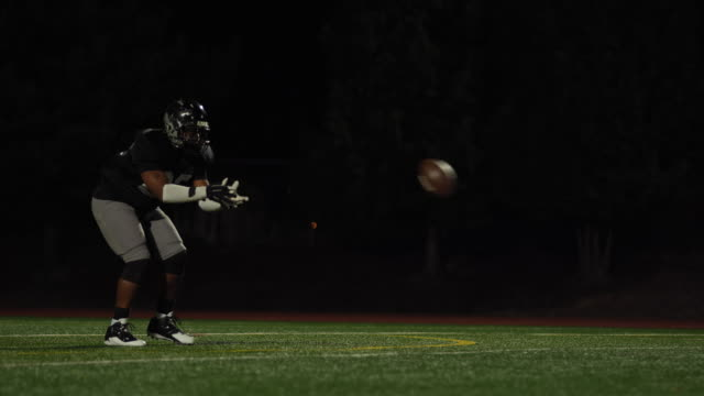A football player catches a ball and kicks it video