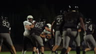 A football player fights his way down the field toward the end zone at night video