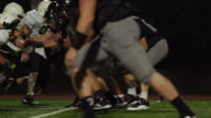 A football player gets unexpectedly tackled soon after the ball is hiked to him video