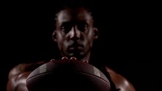 Football player holding ball, shift focus video