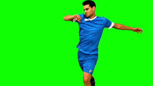 Football player kicking a football on green screen video