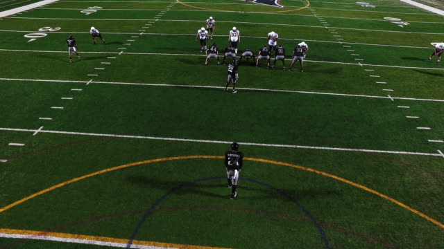 A football player punts the ball during a game, view from above video