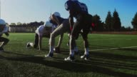 Football players running a play on the field, one player gets tackled video