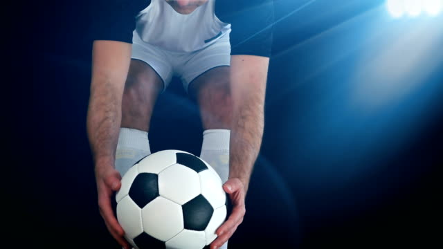 Footballer in boots putting his leg on a ball, black background video