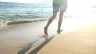 Footprints on shore with woman stepping in distance at sunset video