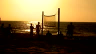 Footvolley. Young people playing footvolley on the sunset beach video