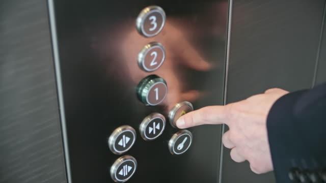 Forefinger pressing alarm button in elevator video