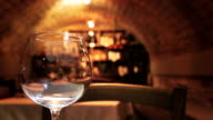 Foreground wine glass and restaurant cavern video