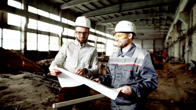 Foreman and chief engineer at the construction site of the factory. The engineer checks the drawing and discusses further plans with the employee video
