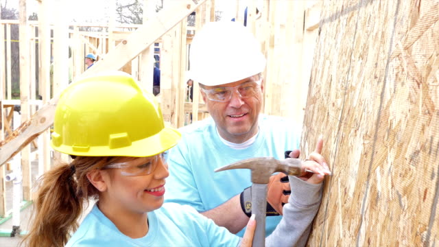 Foreman helps young volunteer as they build home for charity video