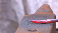 forging hot iron rod on the anvil with a hammer video