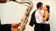 Formal dressed romantc couple with saxophone player video