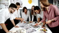 Four architects standing and planning around a table while looking down at blueprint 20s FullHD. video