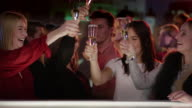 four attractive girls at bar in club raising their champagne glasses video
