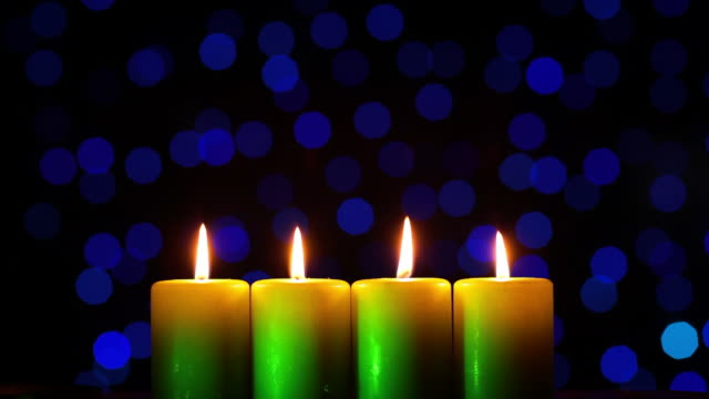Four candles on blurred light background video