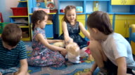 Four children are playing on the floor with toys video