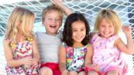 Four Children Relaxing In Garden Hammock Together video
