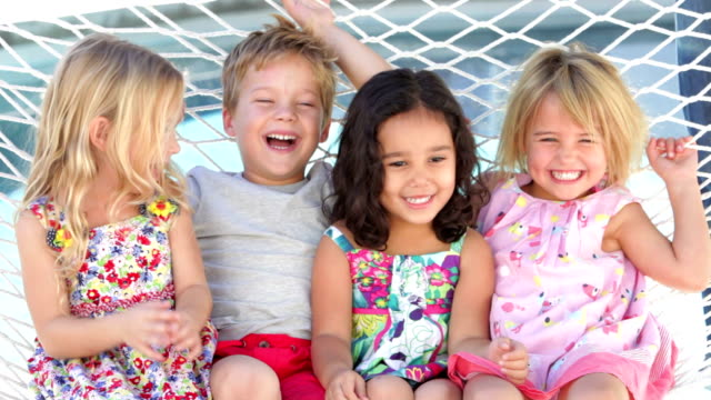 Four Children Relaxing In Garden Hammock Together video