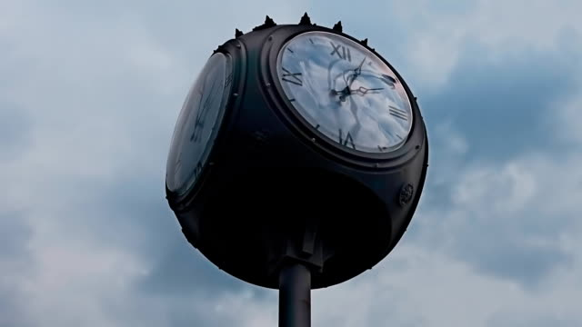 Four dial street clock and moving clouds on a blue sky in time lapse video