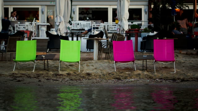 Four empty chaise-lounges on the beach with cafe behind video