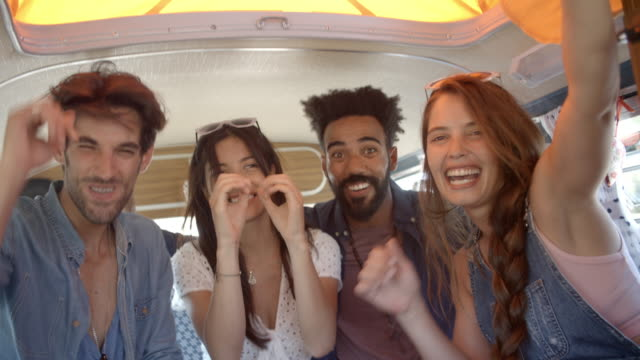 Four excited adult friends on a road trip in a camper van video