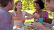 Four friends eating at a table together outdoors video