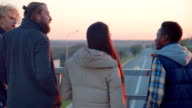 Four friends hanging out on bridge in evening video