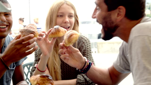 Four friends have italian breakfast eating brioches outdoor CU video