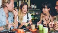 Four friends having breakfast in a coffee shop video