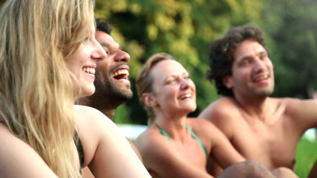 Four friends laughing while sitting in nature video