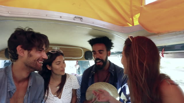 Four friends on a road trip talk in the back of a camper van video