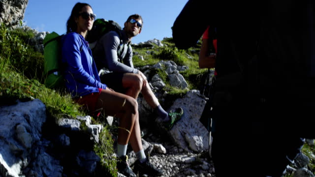 Four friends relax and talk along hiking trail path. Group of friends people summer adventure journey in mountain nature outdoors. Travel exploring Alps, Dolomites, Italy. 4k slow motion 60p video video