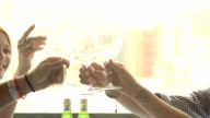 Four friends toast with white wine at italian restaurant CU video
