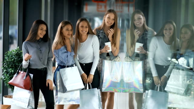Four happy beautiful women shopping and looking at storefronts video