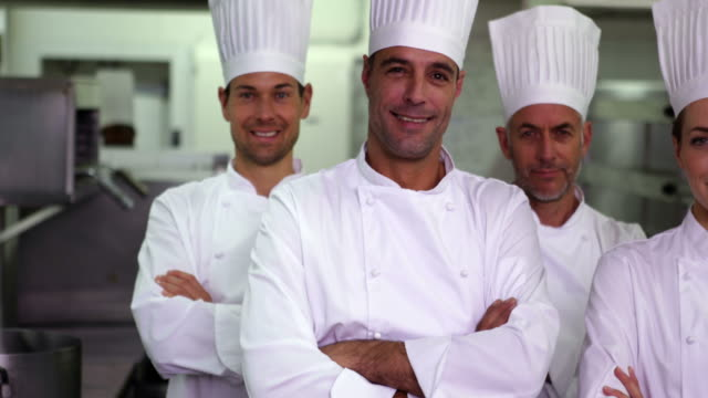 Four happy chefs looking at camera with arms crossed video
