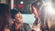 Four happy multi-ethnic women drinking at a party video