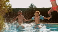 SLO MO DS Four kids jumping into the pool at sunset video