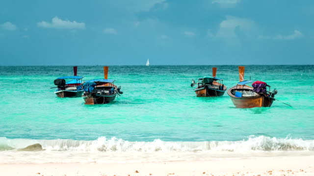Four long-tailed boat swinging in blue waves on Bundhaya beach, and white sail boat on the horizon, Koh Lipe Thailand video
