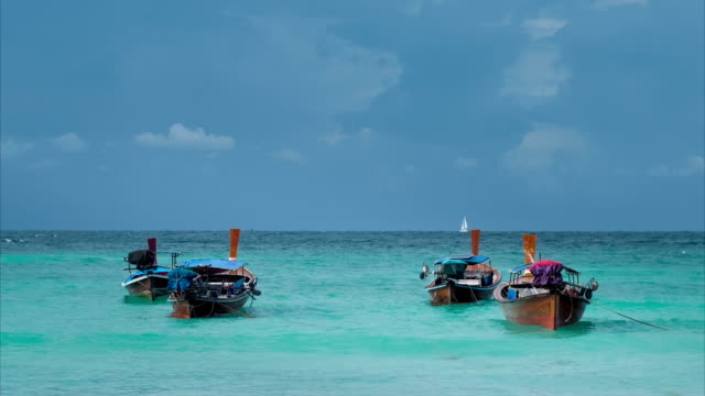 Four long-tailed boat swinging in blue waves, white sail boat on the horizon, Koh Lipe Thailand video