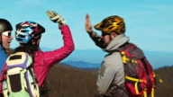 Four mountain bikers stopping and doing high five video