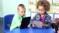 Four multi-ethnic children in schiool using digital tablets video