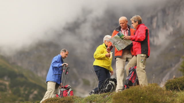 four senior hikers looking at map wide video