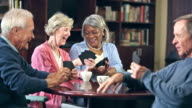 Four seniors drinking coffee, playing card game video