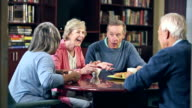 Four seniors drinking coffee, talking, laughing video