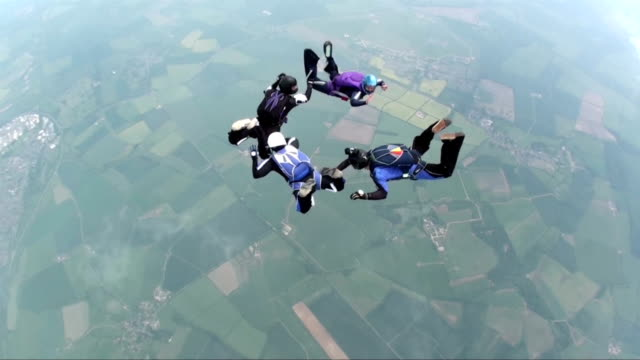 Four skydivers in freefall doing formations video