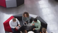 Four students working in the foyer of a university, elevated view, shot on R3D video