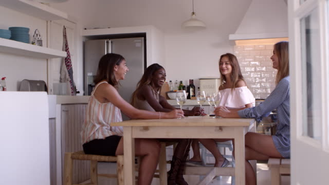 Four women drinking wine and talking during girls' night in, shot on R3D video