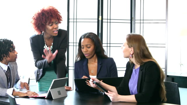 Four young business people in meeting, woman in charge video