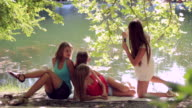 Four young woman photographing in summer park video